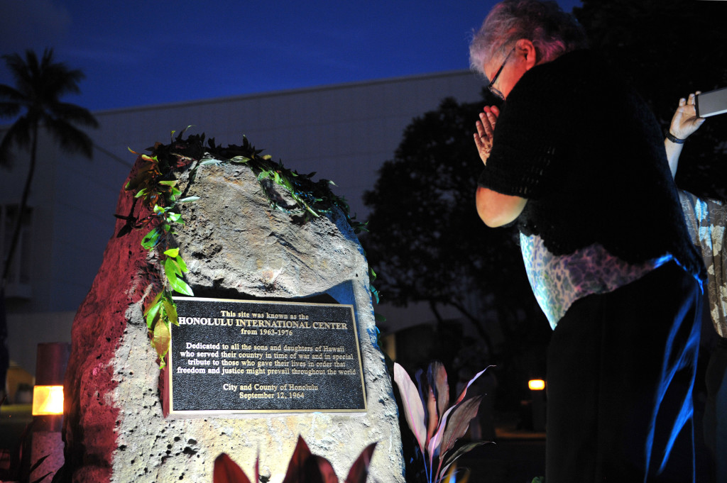 Drusilla Tanaka bows before the war memorial plaque. Johans Chavarro
